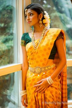 Yellow silk saree with polka dots and green blouse with gold border. Polki jewellery.