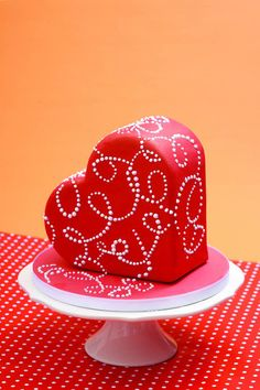 Chocolate cake heart covered with red fondant and decorated with royal icing