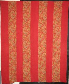 """""""STRIPPY"""" of the most delectable solid red and a paisley print, with very visible quilting patterns on the strips."""