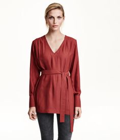 Straight-cut, V-neck blouse in woven fabric with tie belt at waist. Long sleeves with buttons at cuffs. Slits at sides and slightly longer back section.