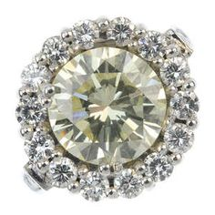 An 18ct gold 'Fancy Light Yellow' diamond and diamond cluster ring.
