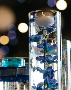 Cylinder vase filled with flowers and floating candle.