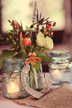 Horseshoe centerpieces for the wedding..... Chris and I like this! Maybe use some from his farm? Then a glass bottle in the middle and two mason jars on the side