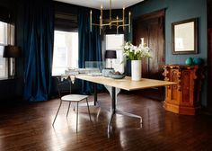 Simple dining room with brass chandelier and blue curtains