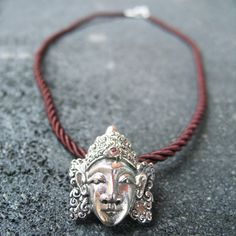 An intricately carved traditional Balinese mask of sterling silver combined with garnet stone and silk cord produce an elegant and unique design to be enjoyed forever.