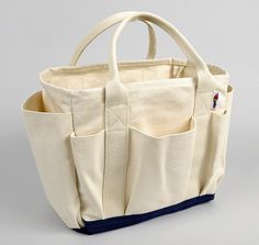 "Utility Tote, Natural/Navy - Heavyweight 18oz cotton duck - Navy blue 18oz cotton duck double bottom - 8 external pockets - Heavy natural cotton webbing handles - Serged interior seams - Made in USA (Greenville, North Carolina) Dimensions: 12""W(at base) x 11""H x 5""D $35.00"