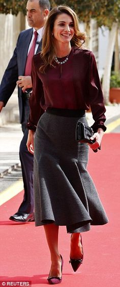 Jordan's Queen Rania power dresses in a wool-blend gray skirt and dark red blouse in Amman...