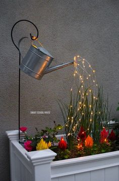 Glowing Watering Can with Fairy Lights - How neat is this? It's SO EASY to make! Hanging watering can with lights that look like it is pouring water. #fairygardening #wateringcans