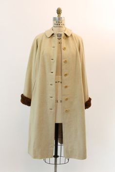 Stunning 1960s Roos Atkins coat! Made in a luxurious ivory cream virgin cashmere. Button down front. Side welted pockets. Plush mink fur adorns the