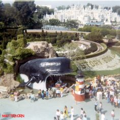 """View from the Skyway, 1971. Guests flock to the Storybook Land Lighthouse ticket booth as a canal boat glides into the open mouth of Monstro. """"it's a small world"""" gleams beyond."""