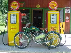Vintage motorized bike in front of Shell gas pumps. Old Gas Pumps, Vintage Gas Pumps, Street Tracker, Cool Motorcycles, Vintage Motorcycles, Bobbers, Shell Oil Company, Motorbike Parts, Pompe A Essence