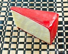 A wedge of Edam cheese with a coating of red wax.