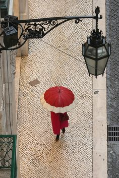 Rainy Day In Lisbon, Portugal. Lisbon is the capital of Portugal. It is the westernmost large city in continental Europe, as well as its westernmost capital city and the only one along the Atlantic coast. Umbrella Art, Under My Umbrella, White Umbrella, Umbrella Street, I Love Rain, Umbrellas Parasols, Singing In The Rain, Street Lamp, Shades Of Red
