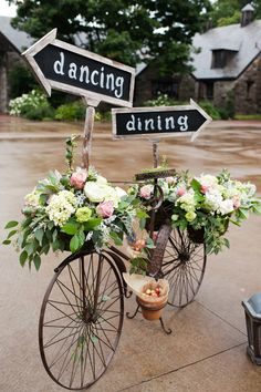Vintage bicycle adorned with flowers and reception signage.