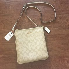 """FLASH SALE NWT Coach Signature Crossbody Authentic Coach Signature NS Crossbody in Light Khaki / Chalk colors!! Retail $195! Has adjustable strap to fit your height and style. Brand new! Never used! Tags still attached! Length 9"""" Width 8"""". Has zipper pocket with little pouch on the inside. Also has a side pocket that snaps shut! NO TRADES. NO LOWBALL OFFERS. NO BUNDLING (Unless with other coach item. If you bundle with other items, I will cancel your order- no discounts). Coach Bags…"""
