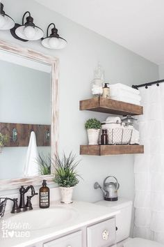 Modern farmhouse bathroom with rustic wood shelving above toilet