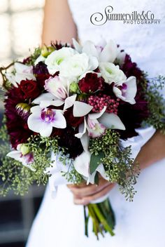 Burgundy dahlias coupled with white cymbidium orchids with their deep red lips are nestled amongst white ranunculus while seeded eucalyptus and pepper berries given it seasonal influence. Created by Adorations.