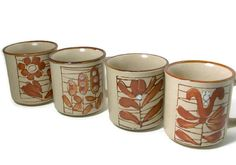 A set of four (4) stoneware mugs, each with a simple floral type design of flower or leaf. Very simplistic in style and color, which is