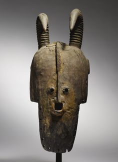 Africa | Proto-Bobo Mask, Burkina Faso. c. prior to 1965. | The form of a domed helmet with extended vertical face in front is frequently seen in Bobo masks, as are small, close-together apertures representing the eyes, and thick, naturalistic, ridged antelope horns.