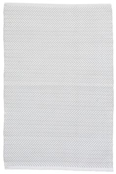 A light grey hue and subtle herringbone pattern make this durable indoor/outdoor rug perfect for both modern and traditional décor styles.