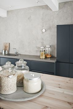 color on cupboards next to concrete and wood, love the canisters on the lazy susan