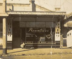 Infant child bending down in a Milk Bar doorway, holding onto the tiled wall shop window for support.  This photograph shows a child playing outside the shop-front of the Atkinson family's new milk bar, Moonee Ponds, 1949. This milk bar was purchased by the Atkinson family only six weeks after migrating from England. The Atkinson family's mother and father had given them some start-up money, 1000  ...
