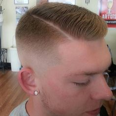 Evenly graduated medium skin fade with a low pomp