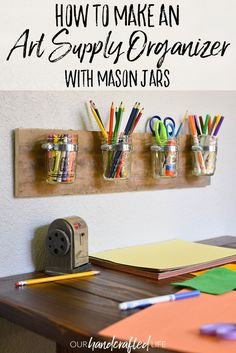 How to make a creative storage solution for kids - DIY Mason Jar Art Supply Organizer. This gorgeous piece is so simple with mason jars, hose clamps, and pallet wood. It becomes a home organizing solution by creating an easy DIY kid's art station or craft corner with craft supply storage. It would go perfectly with a kid's art table in an art center, playroom, or kid's maker space. These glass jars would also be a good bathroom organizer, kitchen organizer, or pantry organizer. This mason…