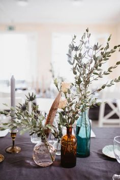 Colored glass & greenery centerpieces | Image by Patrick Karkkolainen