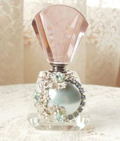 lovely perfume bottle embellished with a pearly blue piece with rhinestones, silver tone accents, and plastic blue flowers with blue rhinestone centers. It is also embellished with enameled light pink flowers with clear rhinestone centers