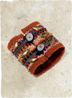 Peruvian Connection Fall 2013The artisan-made cuff is handwoven wool in bright stripes of orange, purple, teal and green wool, embellished in glass and brass beads. Button/loop closure.
