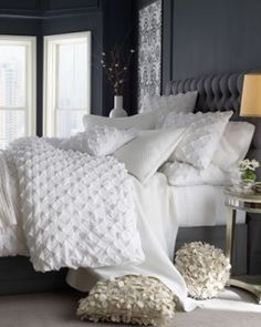 Textured bright white bed linens and deep grey headboard and walls