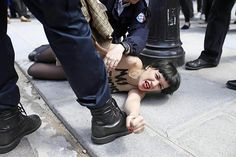 A member of the FEMEN feminist activist group with writing on her chest reading 'May fascists rest in hell' is arrested by police officers in Paris. She had taken part in a protest inside the Notre Dame cathedral against the suicide of a far-right activist