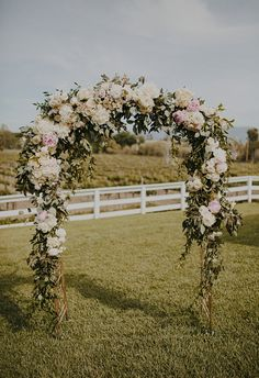 Romantic wrought iron arbor covered with ivory roses, hydrangeas, and greenery // Tyler Branch Photo