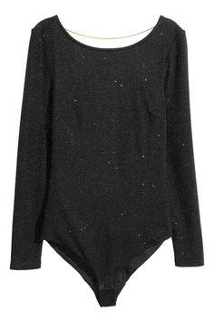 Body glitter: Body a maniche lunghe in jersey con fili glitter e stampa iridescente. Profonda scollatura sulla schiena e catenella metallica orizzontale sulla nuca. Bottoni automatici in basso. Fodera in jersey.