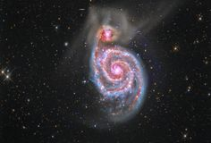 M51 is a spiral galaxy, about 30 million light years away, that is in the process of merging with a smaller galaxy seen to its upper left.
