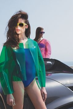 Boxy transparent green vinyl jacket worn over simple blue one-piece swimsuit. Boxy pink clear vinyl jacket worn with purple two-piece. High Fashion, Fashion Show, Fashion Design, Fashion Trends, Womens Fashion, Blue One Piece Swimsuit, Vogue, Beachwear, Swimwear