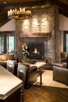 A cozy rustic family room features leather furniture, reclaimed wood floors and beams, a stone fireplace, and a wonderful candle-studded chandelier.