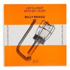 Billy Bragg. Life's a Riot with Spy vs Spy. Utility Records. Designed by Barney Bubbles.