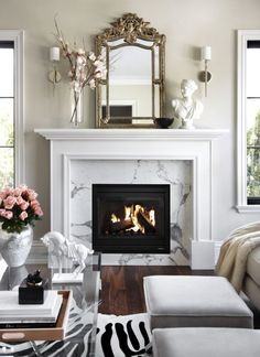 White marbled fireplace with antique mirror and zebra rug.