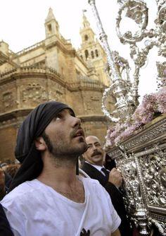 Sevilla, Un costalero durante el cambio de cuadrilla del palio de la Hermandad sevillana de El Cerro a su salida de la Catedral y con la Gir...