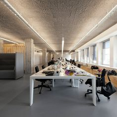 A huge table features inside this office, which runs beneath a rows of windows.