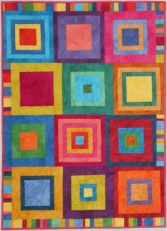 """Each 12"""" block is a different set of fabrics. We pieced random sized strips for the side borders and the inserts that offset the blocks. No exact pattern for this new fun; the blocks are from the Yikes pattern but the fabric requirements are different than the pattern calls – this is for you if you can work with what you already have! 52"""" x 38"""" as shown with 23 colors. Windham Palette by Marcia Derse, quilted by Kars Quilting."""