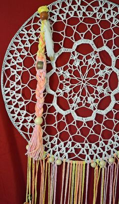 This is a vintage crochet 17 round Dream Catcher. White/Light color would look great on any wall in any room. This piece is a beautiful display of vintage style mixed with native style. The fringe is made from hand dyed cotton yarn in a colorful display of dreamy colors.  Made out of cotton thread with hand dyed cotton yarn fringe, wooden beads and gold tipped white feathers. Light weight and elegant.  Gift Ideas: Wedding, Birthday, Anniversary, House Warming, Holidays  Care instructions...