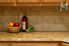 The light tumbled stone backsplash compliments the yellow tones in the Golden Valley granite.