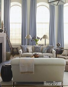 A Soothing Living Room  Grandly arched windows in the 18-foot-high living room, designed by Christopher Maya, are framed by the icy blue of Holland & Sherry Glace curtains in Glacier. Maya designed the sofas and had throw pillows made from antique Fortuny fabric