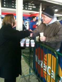 Cubs board member Laura Ricketts gives coffee to fans as they wait to buy tickets on a chilly morning at Wrigley Field (March 9, 2012).  from@cubs