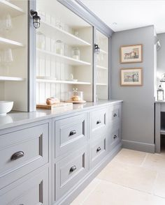 LOVE this long wall of gray cabinets with bead board in back and sconces in between.