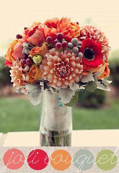 Des renoncules orangés, des dahlias aux tons feu tout en dégradé, des anémones rouges et leur coeur noir, des baies de Brunia, et quelques petites baies rouges pour ce bouquet de mariée aux couleurs de l'automne tout en relief.