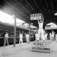 Passengers on a train traveling from Tokyo to Osaka go through three minutes of calisthenics under leadership of a drill master, during a five-minute stopover at Hammamatsu on August 1952 by Max Desfor/AP Photo Hamamatsu, Picture Company, Photo U, The Second City, Iwo Jima, The Longest Journey, Japan Photo, Hiroshima, Historical Pictures